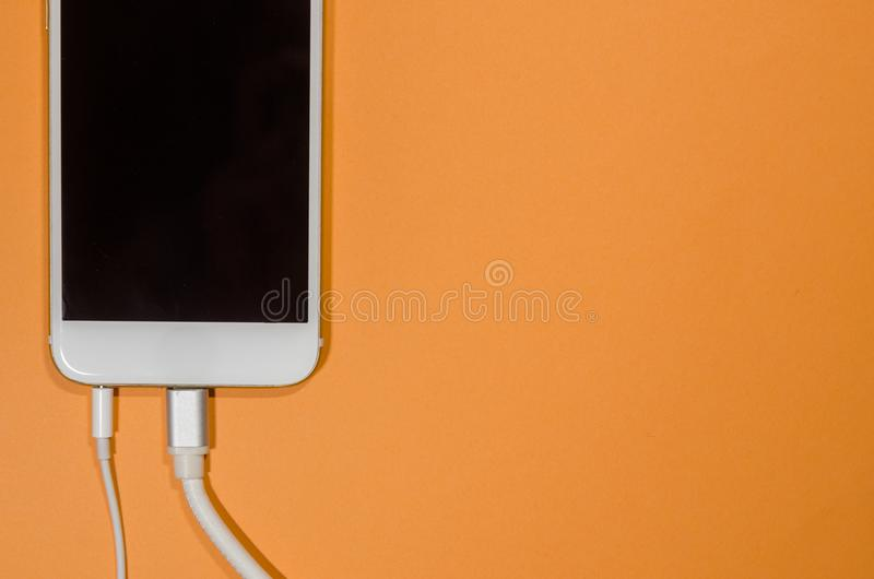 A phone with usb cable and headphones royalty free stock photo