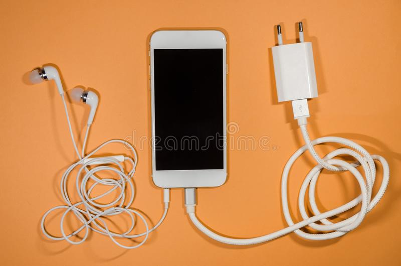 A phone with usb cable and headphones stock image