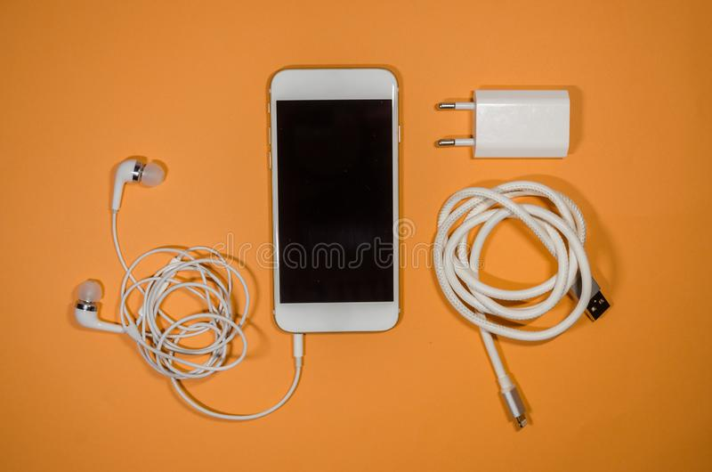 A phone with usb cable and headphones stock images