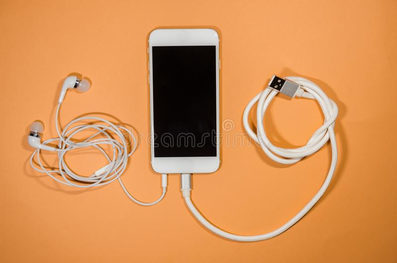 A phone with usb cable and headphones stock photo