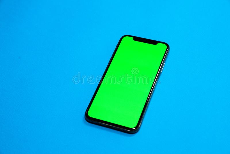 Phone XS, Phone smartphone, green screen on Blue background royalty free stock photos
