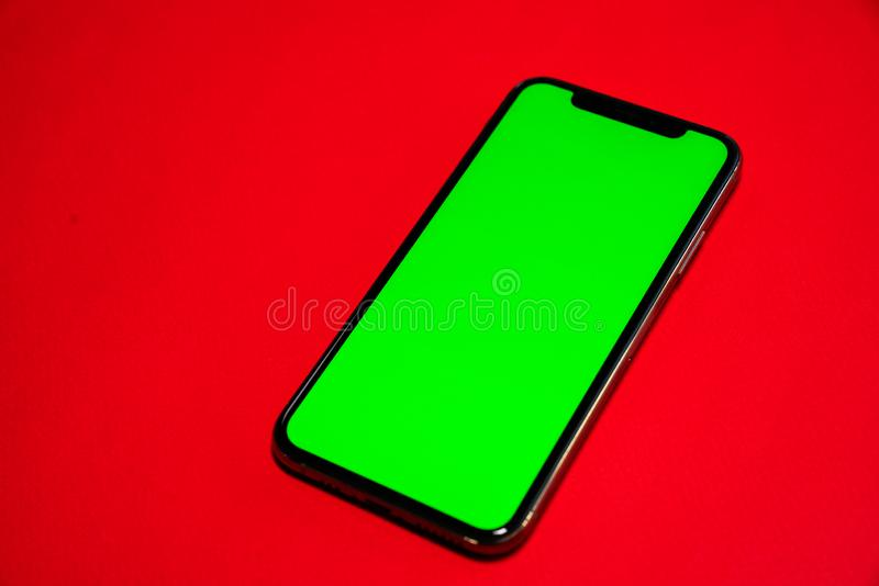 Phone XS, Phone smartphone, green screen on Red background royalty free stock photos
