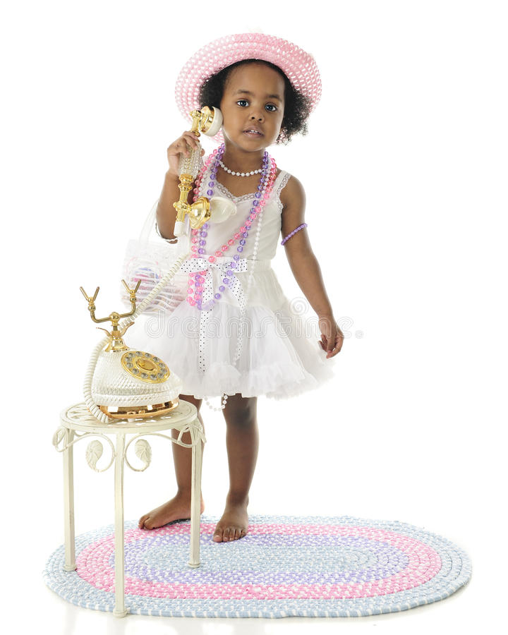 The Phone is for You. An adorable 2 year old diva calling the viewer to her fancy French phone. She wears a white slip and petticoat, and pastel hat and beads royalty free stock photos