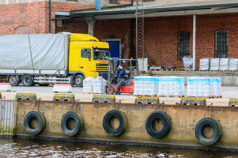 Phonecall. Karlshamn, Sweden - May 06, 2015: Unknown male forklift driver making a phonecall while unloading pallets at the docks. Truck and building in stock images