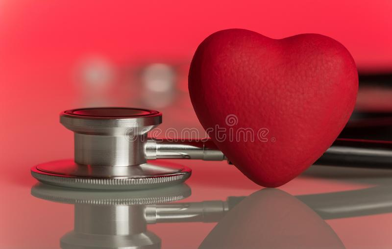 Phonendoscope and artificial heart, on pink. Phonendoscope and artificial heart on a bright beautiful pink background stock photo