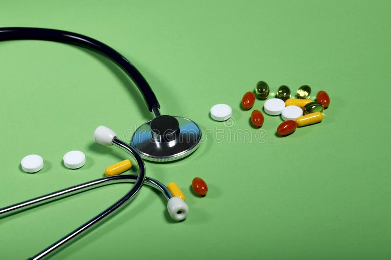 Phonendoscope and colored pills and capsules on a green background. Side view, close-up, free space stock image