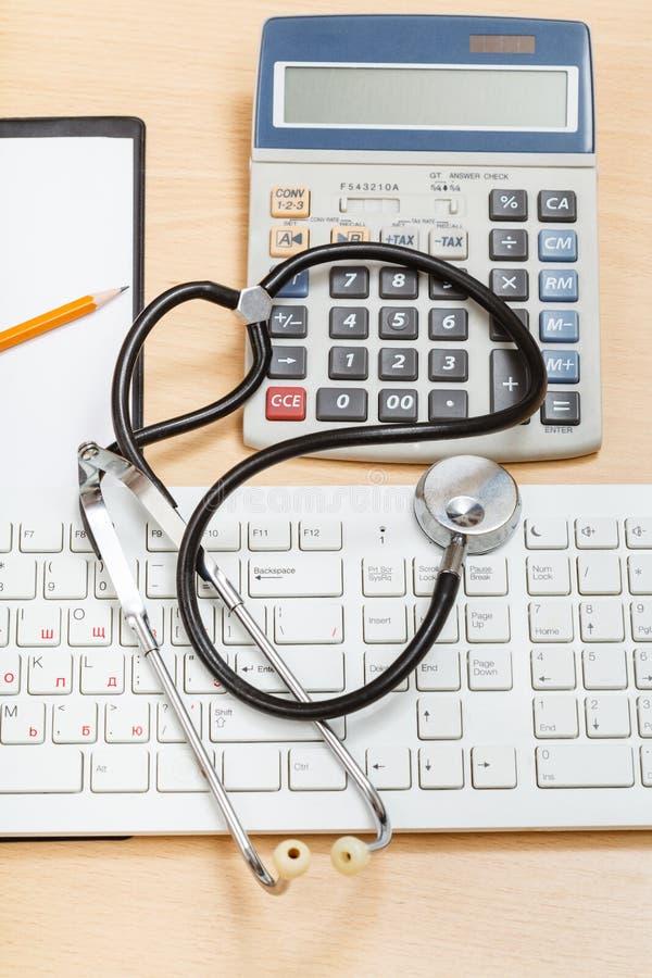 Phonendoscope on keyboard, calculator, clipboard. Medical still life - phonendoscope on white keyboard, calculator and blank clipboard stock photos