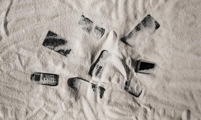 Phones and touch screen devices under the sand. On the beach stock images