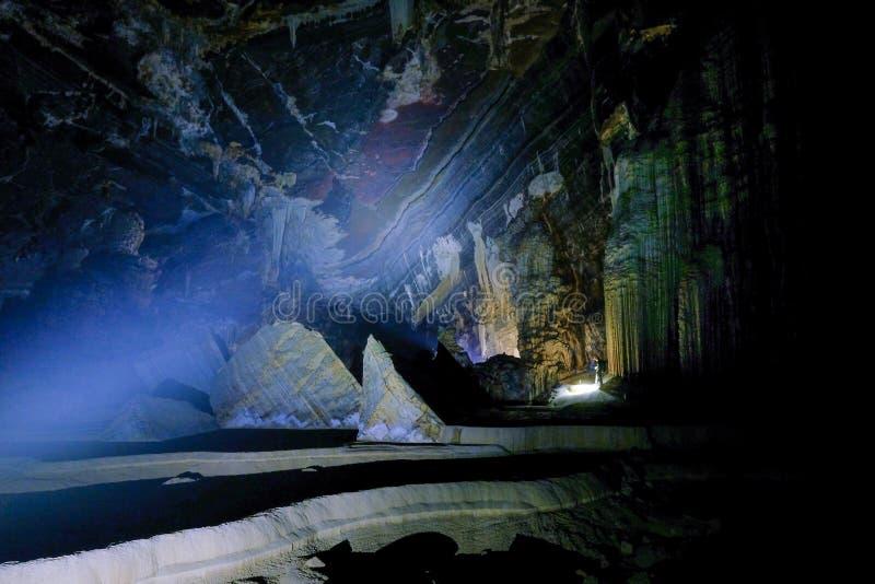 Phong Nha Ke国立公园/越南,16/11/2017:有站立在吊连队洞里面的巨型钟乳石旁边的前灯的人 库存照片