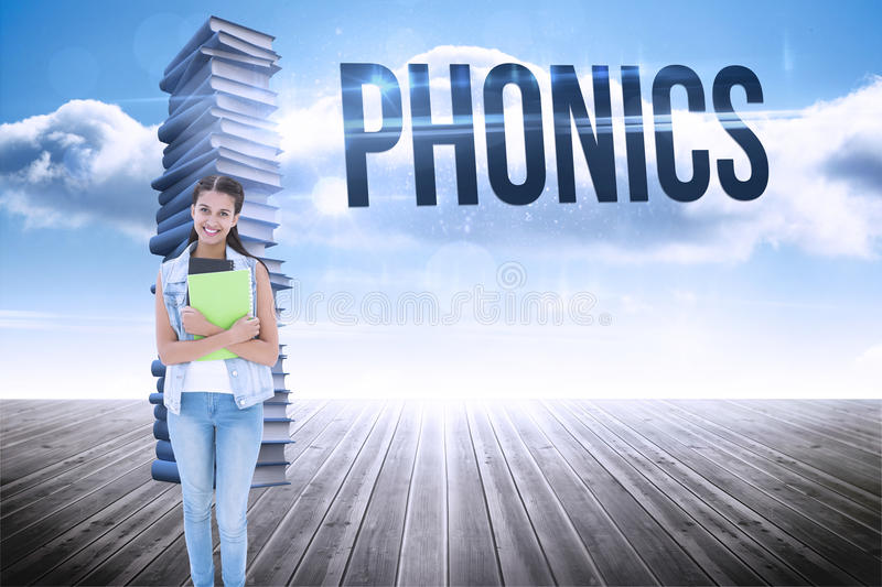 Phonics against stack of books against sky. The word phonics and student holding notepads against stack of books against sky stock photography