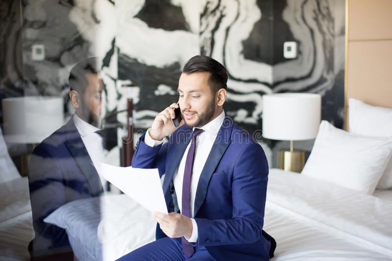 Phoning to business partner. Successful broker or financier in suit reading terms of new financial contract to business partner by smartphone while sitting on royalty free stock image