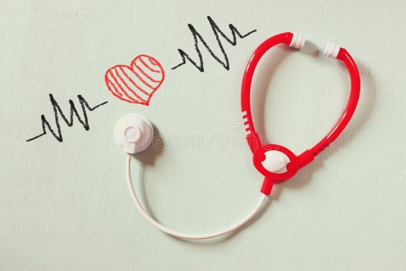 Phot in bianco e nero dello stetoscopio del giocattolo e dell'illustrazione variopinta dei battiti cardiaci sopra fondo struttura fotografia stock