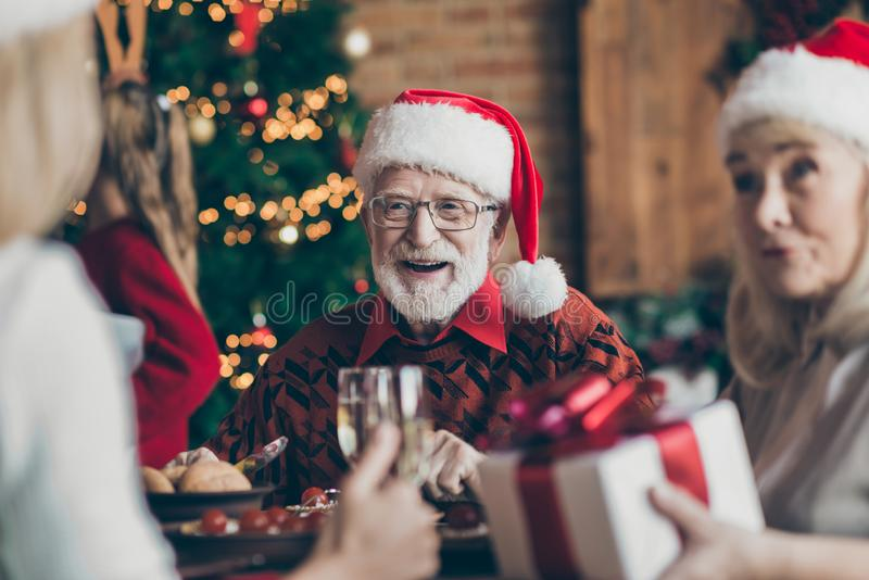 Phot of grandfather positive cheerful smiling in eye glasses spectacles wearing santa hat headwear feeling festive mood royalty free stock photo