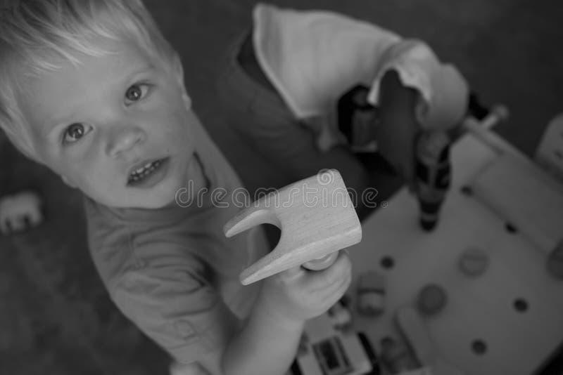 Photo à fond gris de garçon sur le T-shirt tenant le bois de Brown photographie stock libre de droits