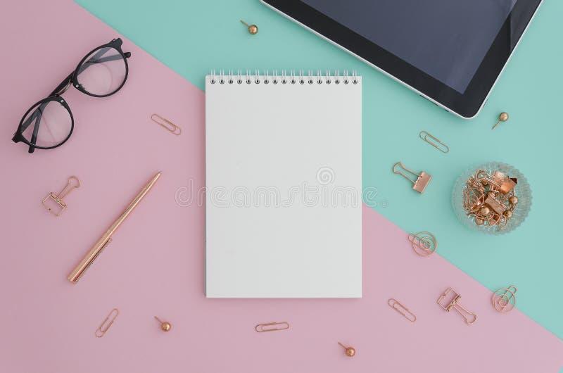 Photo étendue plate créative de bureau d'espace de travail avec le comprimé, les lunettes, les accessoires d'or et le carnet avec photo stock