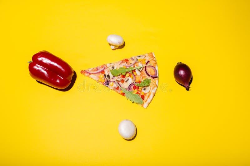 Photo étendue plate de tranche de pizza et légumes placés autour de d'isolement sur le fond jaune image stock