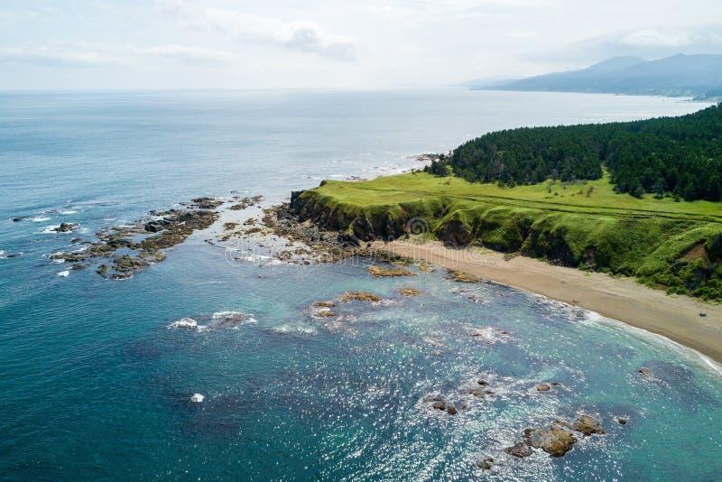 Photo aérienne de bourdon de cap Ptichiy, île de Sakhaline, Russie Sahalin de Velikan de cap tout près Pelouses vertes naturelles photographie stock libre de droits