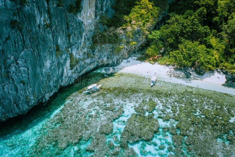 Photo aérienne des bateaux de banca amarrés à la plage blanche et aux personnes de paradis de sable naviguant au schnorchel au-de image libre de droits