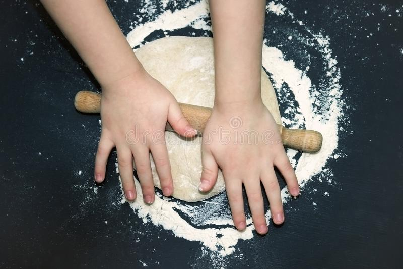 A photo from above of Kid`s hands, some flour, wheat dough and rolling-pin on the black table. Children hands kneading the rye do. Ugh for backing bread. Little royalty free stock photo