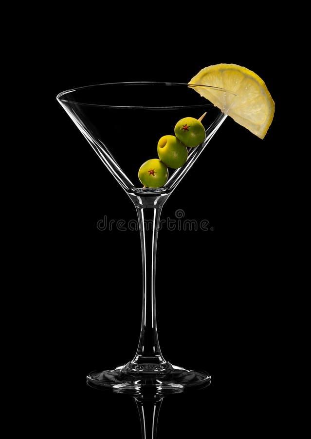 Photo abstraite de verre vide de martini avec des olives Sur un fond noir images stock