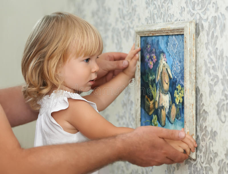 Photo accrochante de père et d'enfant sur le mur vide photos stock