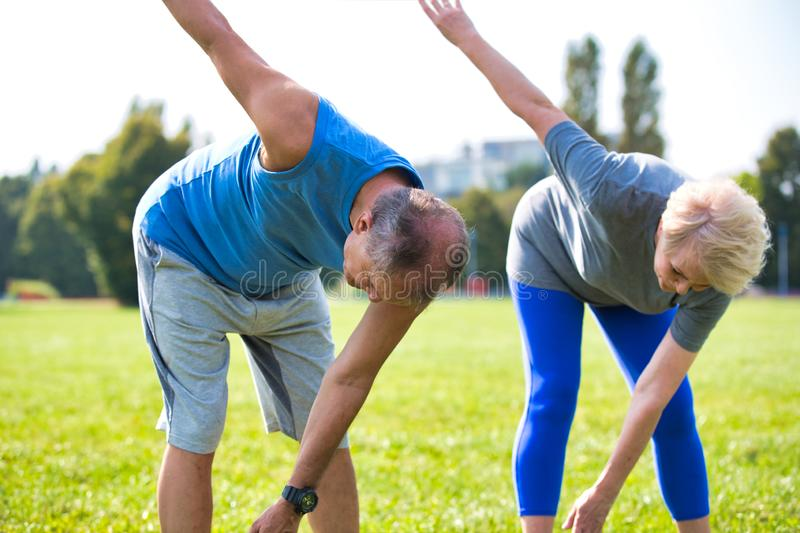 Active flexible senior couple stretching leg in park on sunny day stock images