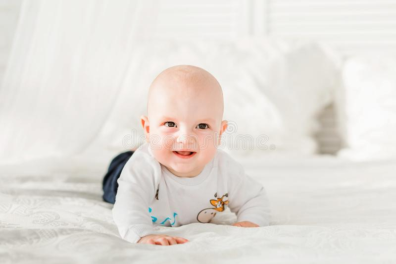Adorable baby boy lying on his stomach and smiling. Photo of Adorable baby boy lying on his stomach and smiling royalty free stock images