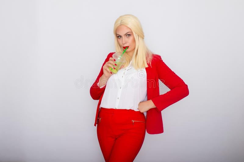 Photo of adorable blonde businesswoman smiling and holding cup of vitamin water stock photography
