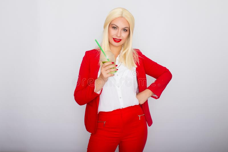 Photo of adorable blonde businesswoman smiling and holding cup of vitamin water stock photos