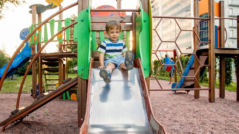 Photo of adorable smiling boy climbing and riding on slide. Active child having fun and playing at park stock image