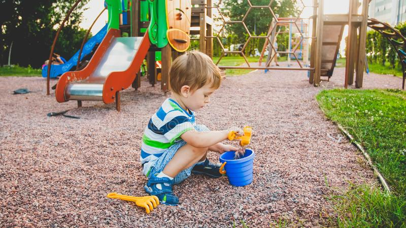 Photo of adorable 3 years old little boy sitting on the playground and digging sand with small plastic shovel and bucket royalty free stock photos