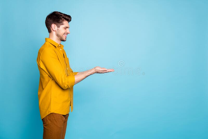 Photo of adoring man holding object with hands wearing yellow shirt trousers pants smiling toothily with eyes closed. Photo of adoring man holding object with stock images