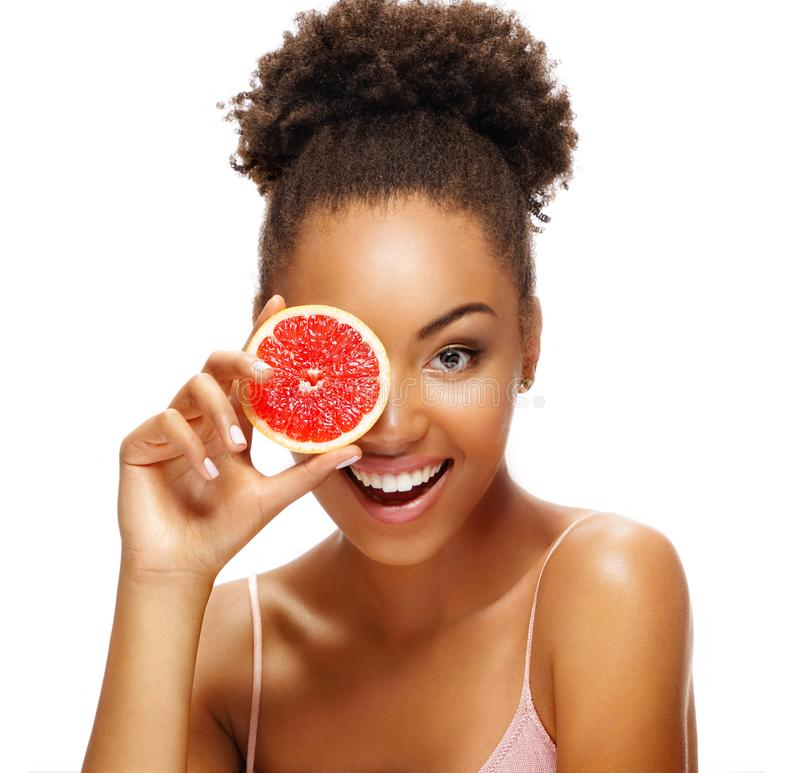 Photo of african american girl holding a half of pomelo in front of her face and smiling on white background stock photo
