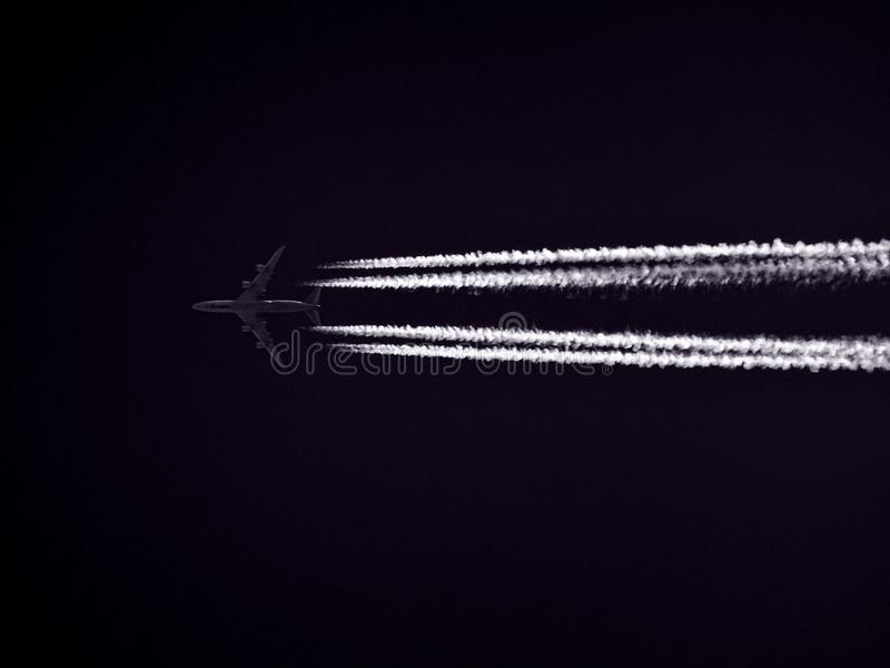 Photo of Airplane Across the Clouds during Night Time stock image