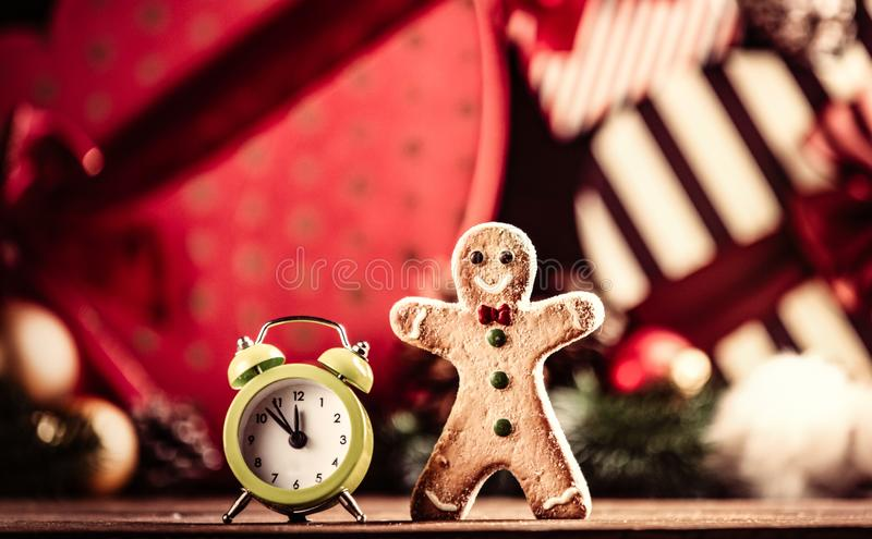 Gingerbread man and alarm clock. Photo of the alarm clock and gingerbread man on the christmas decorations background stock photography