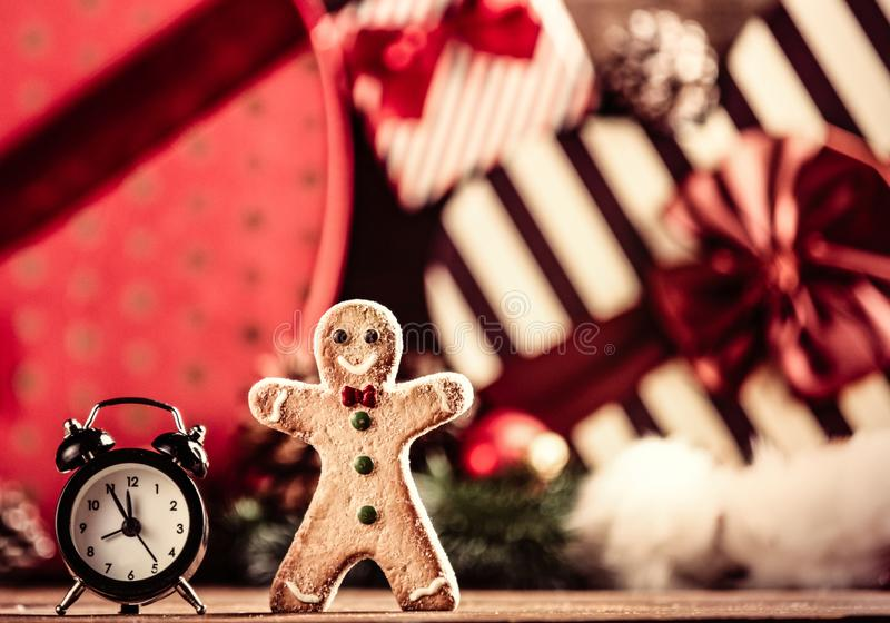 Gingerbread man and alarm clock. Photo of the alarm clock and gingerbread man on the christmas decorations background royalty free stock images