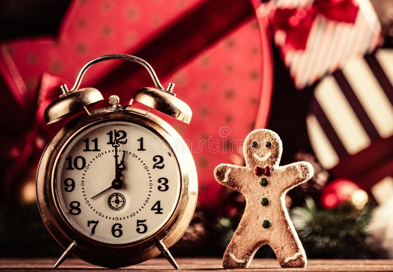 Gingerbread man and alarm clock. Photo of the alarm clock and gingerbread man on the christmas decorations background royalty free stock photo