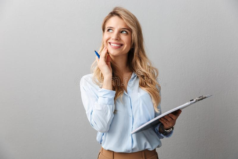 Photo of alluring blond secretary woman with long curly hair thinking and holding clipboard while working in office. Isolated over gray background royalty free stock photos