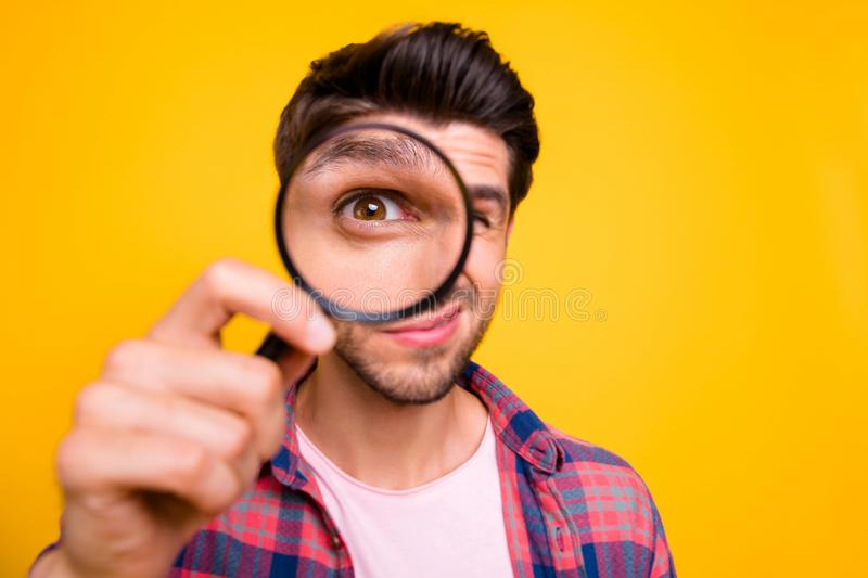 Photo of amazed man trying to see microorganisms with loupe but he evidently cannot manage to do it while isolated with. Photo of amazed man trying, to see royalty free stock image