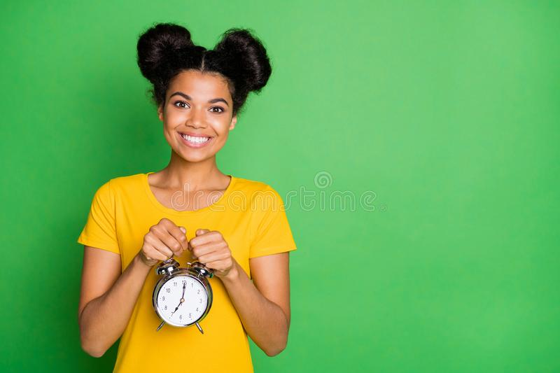 Photo of amazing dark skin lady holding big metal alarm clock recommending for using people who hardly waking up. Mornings wear, casual yellow t-shirt  green stock photos