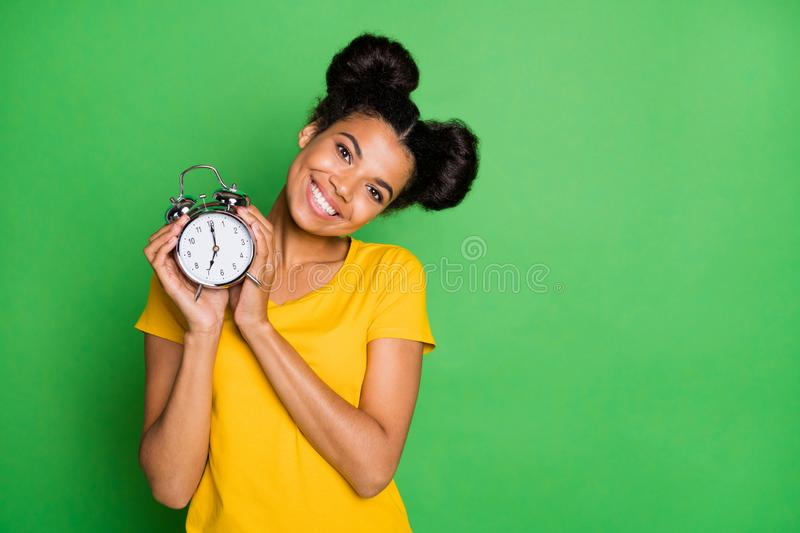 Photo of amazing dark skin lady holding big metal alarm clock recommending for using people who hardly waking up. Photo of amazing dark skin lady holding big royalty free stock images