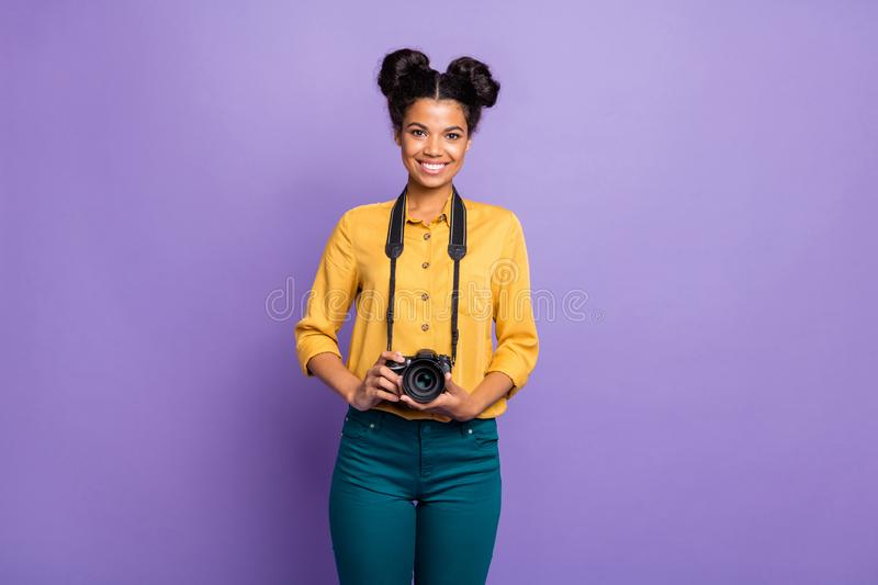 Photo of amazing dark skin lady holding photo digicam in hands positive cheerful mood photographer wear yellow shirt stock photography