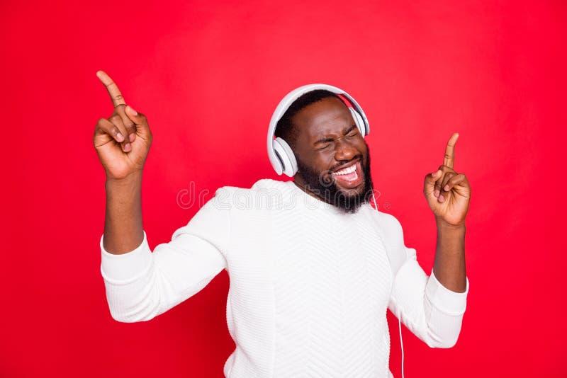 Photo of amazing dark skin man listening favorite playlist in earflaps enjoy best song moment rhythm wear white knitted. Photo of amazing dark skin man listening royalty free stock photos
