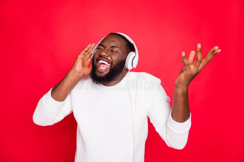 Photo of amazing dark skin man listening to favorite playlist in earflaps crazy singing cool track wear white knitted. Photo of amazing dark skin man listening royalty free stock image