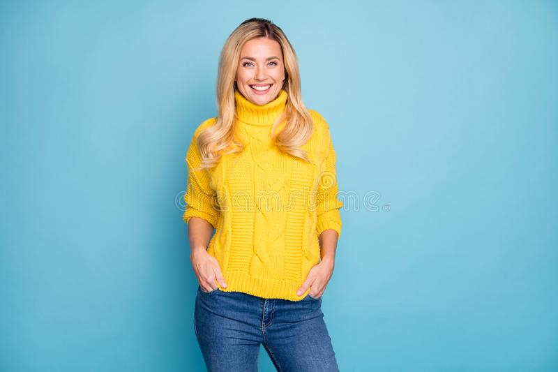 Photo of amazing pretty blond lady toothy smiling good mood holding hands in pockets wear warm knitted yellow jumper. Photo of amazing pretty blond lady toothy royalty free stock photography