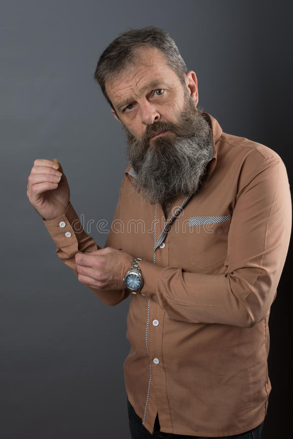 Photo of an angry grumpy old man looking very displeased. Male man with long beard on his face. Close up face . stock photography