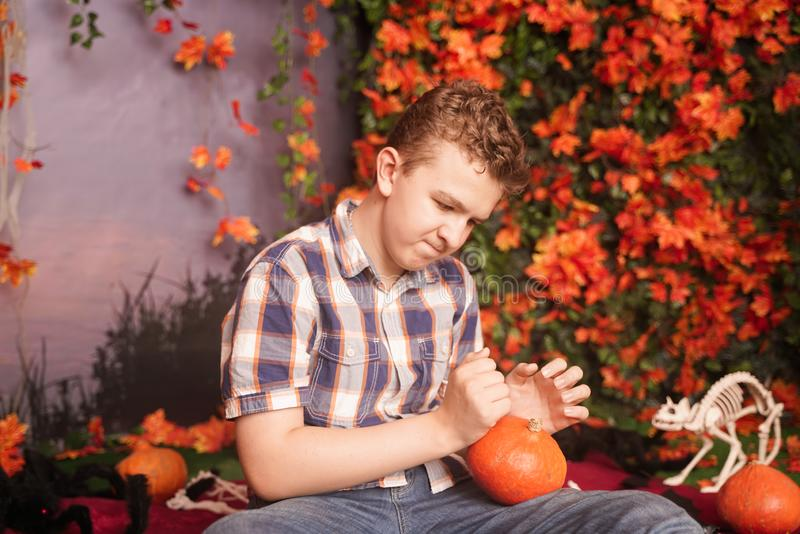 Photo of angry young man on halloween wearing classical plaid shirt holding orange pumpkin over street background with. Autumn leaves stock images