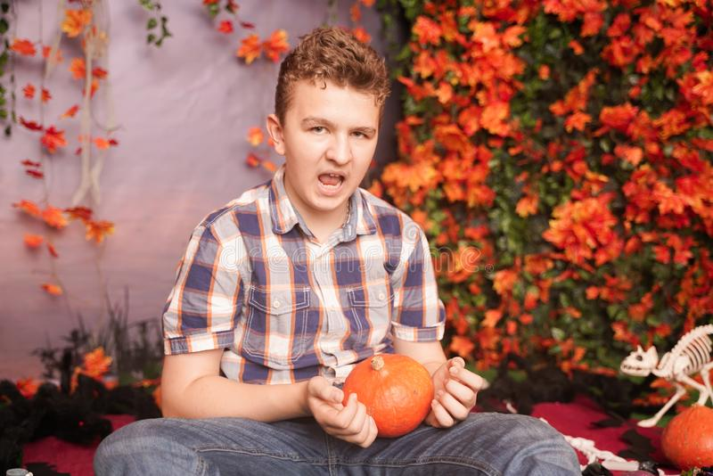 Photo of angry young man on halloween wearing classical plaid shirt holding orange pumpkin over street background with. Autumn leaves stock photography