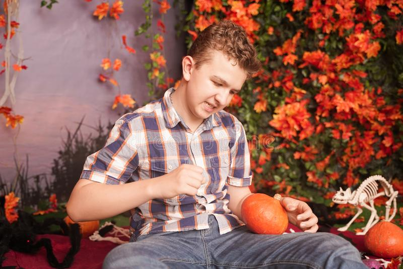 Photo of angry young man on halloween wearing classical plaid shirt holding orange pumpkin over street background with. Autumn leaves stock photos