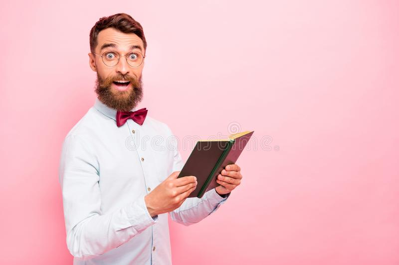 Photo of astonished excited cheerful rejoicing positive glad scientist genius holding opened paper literature in hands. Photo of astonished excited cheerful stock photo